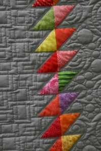 gray quilt with colored triangles